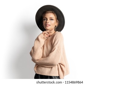 Portrait of romantic girl in knitted warm sweater on white background. Pretty young female wearing modern autumn outfit. Warming up and youth concept.