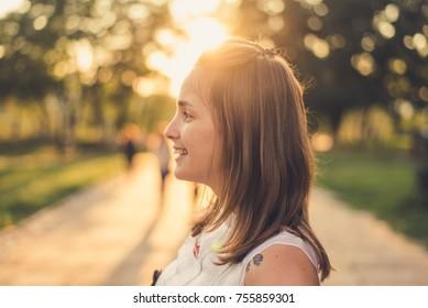 Portrait of romantic girl in the park in sunset light