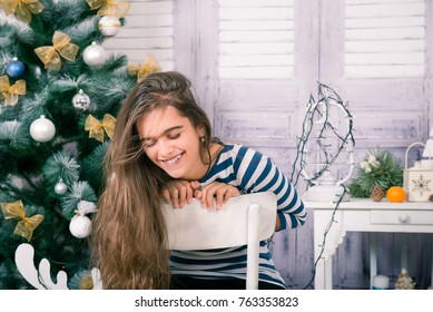 portrait of a romantic girl in a room of blue and white interior. girl in background New Year's interior. Beautiful girl in christmas and new year. young girl with long hair sitting on chair.