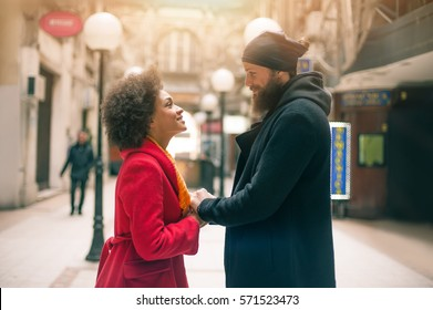 Portrait of romantic multiethnic couple in love hugging on the street. Falling in love