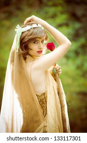Portrait of romantic woman in fairy forest with a rose