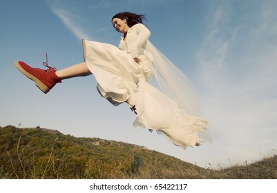Portrait of romantic woman jumping on field