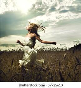 Portrait of romantic woman running across field