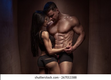 Portrait of a Romantic Young Bodybuilding Couple with Sexy Bodies Posing so Closed Against a Brown Wooden Wall Background