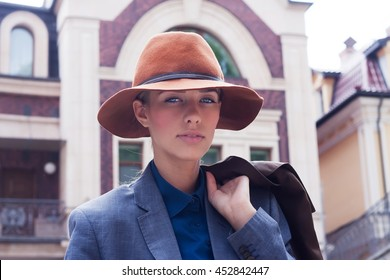 Portrait of a romantic young business woman in a hat against the backdrop of the old town