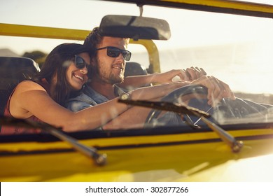 Portrait of romantic young couple going on a long drive in open car on a summer day. Handsome young man with his beautiful girlfriend on a road trip.