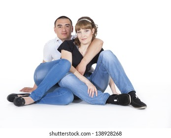 Portrait of a romantic young couple sitting together on a white background, they have a wedding tomorrow
