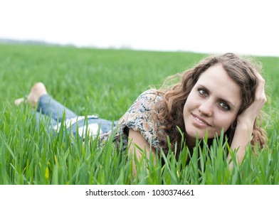 portrait of romantic, young woman with short hair lying on green grass (meadow, prairie) barefoot, dreams