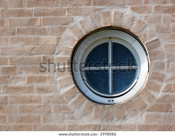 portrait of round window and a modern yellow brick wall