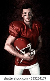 Portrait of rugby player posing with helmet against dark background