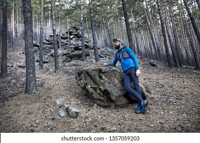 Portrait of runner athlete with beard in blue sport costume near big stone in the forest