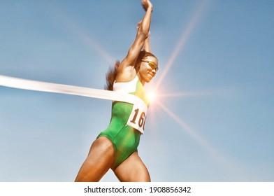 Portrait of Runner Breaking Finish Line Tape