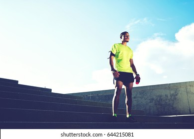Portrait of a runner man with armband on the arm rest after jogging while standing on ladder against the sky background with copy space area for your text message information,sportsman taking a break