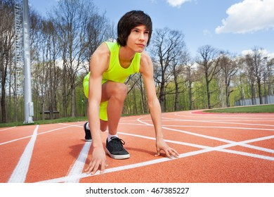 Portrait of runner in start position ready to race