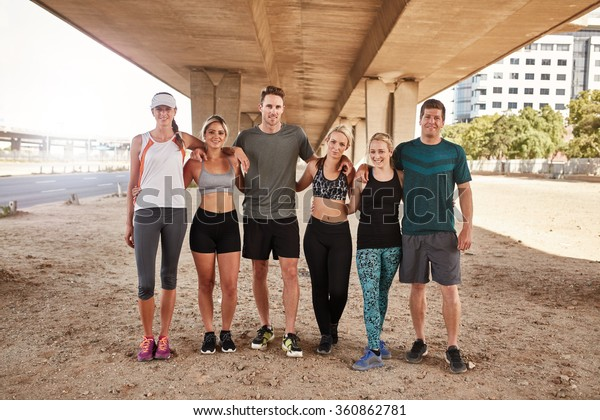 Portrait of running club group standing together and posing for camera. Healthy young men and women training outdoors.
