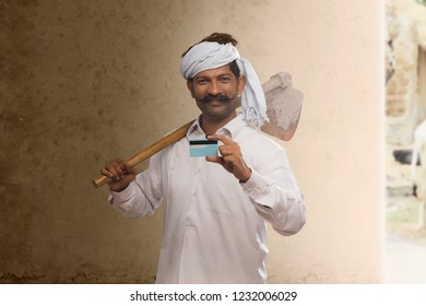 Portrait of rural farmer holding credit card and carrying hoe on his shoulder