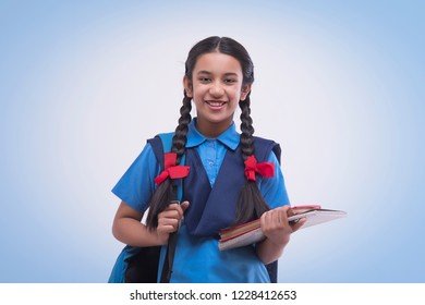 Portrait of rural school girl in uniform holding book and bag