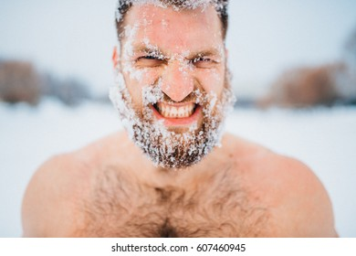Portrait of russian bearded bodybuilder standing without clothes outdoors in winter on a frozen snowy lake with different emotions and posing for camera