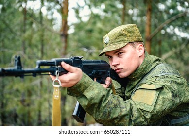Portrait of a Russian soldier in modern military uniforms and weapons, machine gun. Green form