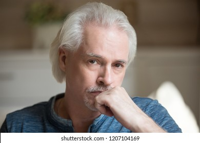 Portrait of sad aged man looking at camera thinking about life difficulties or problems, upset senior male pondering or considering something, thoughtful elderly husband making picture at home