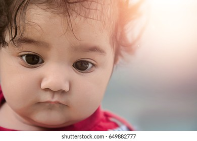 Portrait of sad Asian baby on blur background.