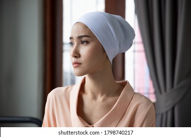 Portrait of sad asian woman cancer patient wearing head scarf after suffering serious hair loss due to chemotherapy