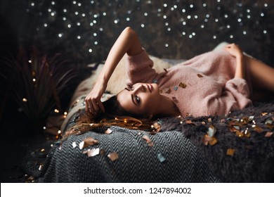 Portrait of sad attractive young woman with tinsel confetti and garland lights celebrating alonein dark room. New year's feeling. Merry christmas
