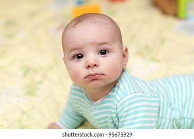 Portrait of sad baby boy at home