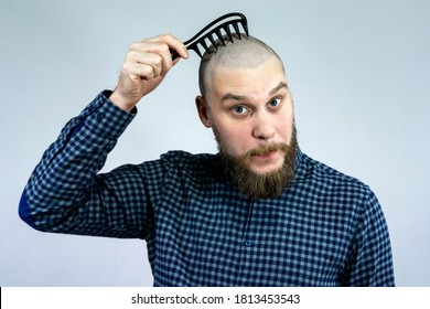 Portrait of sad bearded bald guy holding a comb in his hand. The concept of hair loss and hair transplantation