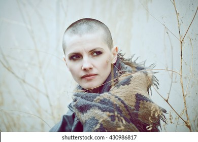 Portrait of sad beautiful Caucasian white young bald girl woman with shaved hair head in leather jacket and scarf shawl looking away, toned with Instagram filters in blue green color