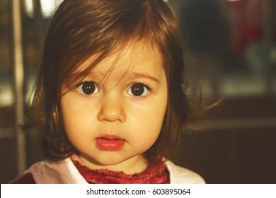 Portrait of a sad beautiful little girl close-up. Toned