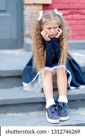 Portrait of a sad beautiful young schoolgirl is crying at the door of the school. does not want to go to school Farewell Bell. day of knowledge. beginning of the school year.