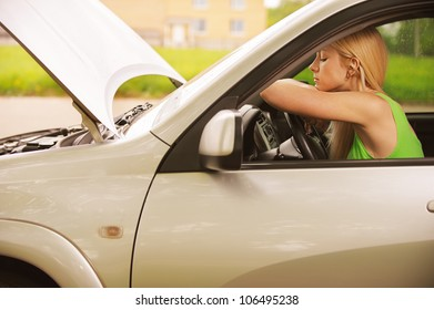 Portrait of sad beautiful young woman in car.