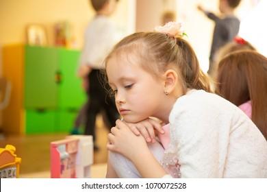 Portrait of sad blond little girl sitting in kindergarten