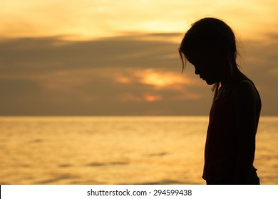 Portrait of sad blond little girl standing on the beach at sunset time.