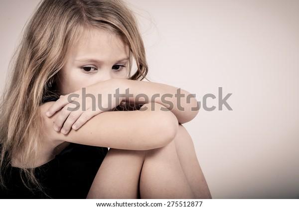 Portret van triest blond meisje in de buurt van witte muur