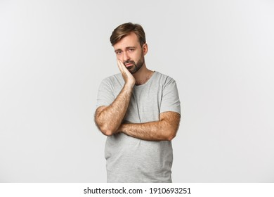 Portrait of sad and bored bearded man in gray t-shirt, leaning on palm and looking reluctant, standing over white background