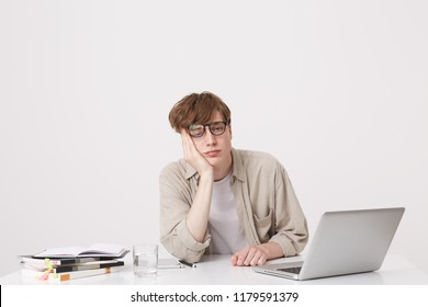 Portrait of sad bored young man student wears beige shirt and spectacles looks tired sitting at the table with laptop computer and notebooks isolated over white background