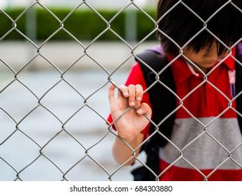 Portrait sad boy behind fence mesh netting. Emotions concept - sadness, sorrow, melancholy.