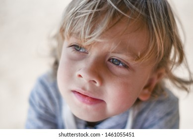 Portrait of a sad brooding boy against the sand. Lonely child walking on the beach. Blond baby looking into the distance.