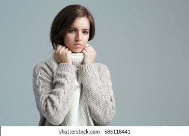 Portrait of the sad brunette girl in a sweater on a gray background. She does gestures by hand.