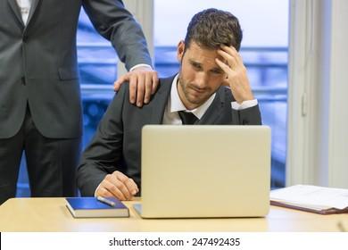 Portrait of sad businessman with her boss at background. Hand on shoulder