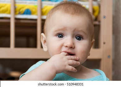 Portrait of sad charming baby with finger in his mouth.