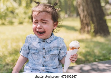 Portrait of sad crying child with ice-cream cone in hand in the park. Little cute girl toddler frustrated to eat dessert outdoor against nature background. Sad expression. Childhood.