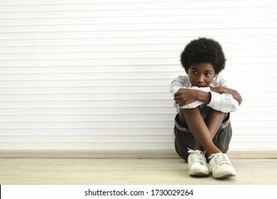 Portrait of sad depressed black african american cute little boy child  alone sitting on floor at home