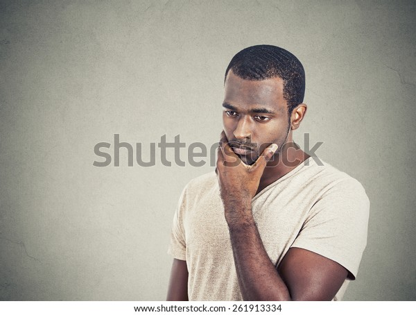 Portrait sad, depressed, worried young man looking down isolated on grey wall background. Human face expressions, emotion, feelings, reaction, life perception
