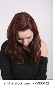 PORTRAIT OF SAD DEPRESSED YOUNG WOMAN WITH DARK RED HAIR WITH HEAD BOWED DOWN. WORRIED.