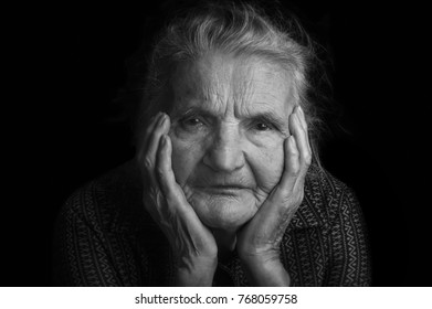 Portrait of a sad elderly woman. Dreaming the past. Selective focus.