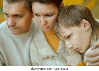 Portrait of a sad family of three on the nature