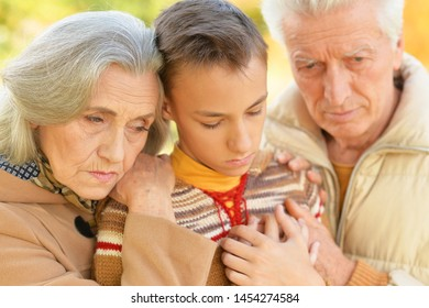 Portrait of sad grandfather, grandmother and grandson hugging